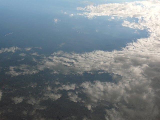 Blauer Himmel und Wolken spiegeln sich im Wasser